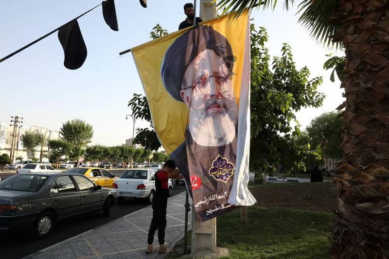 Two workers hang a banner of the presidential candidate Ebrahim Raisi, currently judiciary chief, near his campaign rally in town of Eslamshahr southwest of the capital Tehran, Iran, Sunday, June 6, 2021. Iran will hold presidential elections on June 18 with 7 candidates approved by the Guardian Council. (AP Photo/Vahid Salemi)