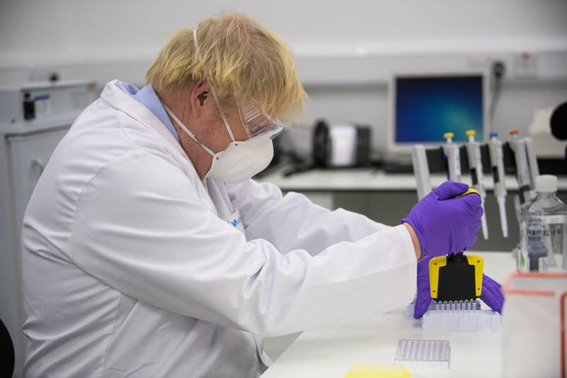 Britain's Prime Minister Boris Johnson tries a test as he visits the French biotechnology laboratory Valneva in Livingston, west Scotland, on January 28, 2021 where they are set to start large-scale manufacturing of a Covid-19 candidate vaccine. - Johnson visited Scotland on January 28 where he rejected calls for a second referendum on independence in Scotland, stating the case for a continued United Kingdom by the joint effort to combat the coronavirus outbreak. (Photo by Wattie Cheung / POOL / AFP)
