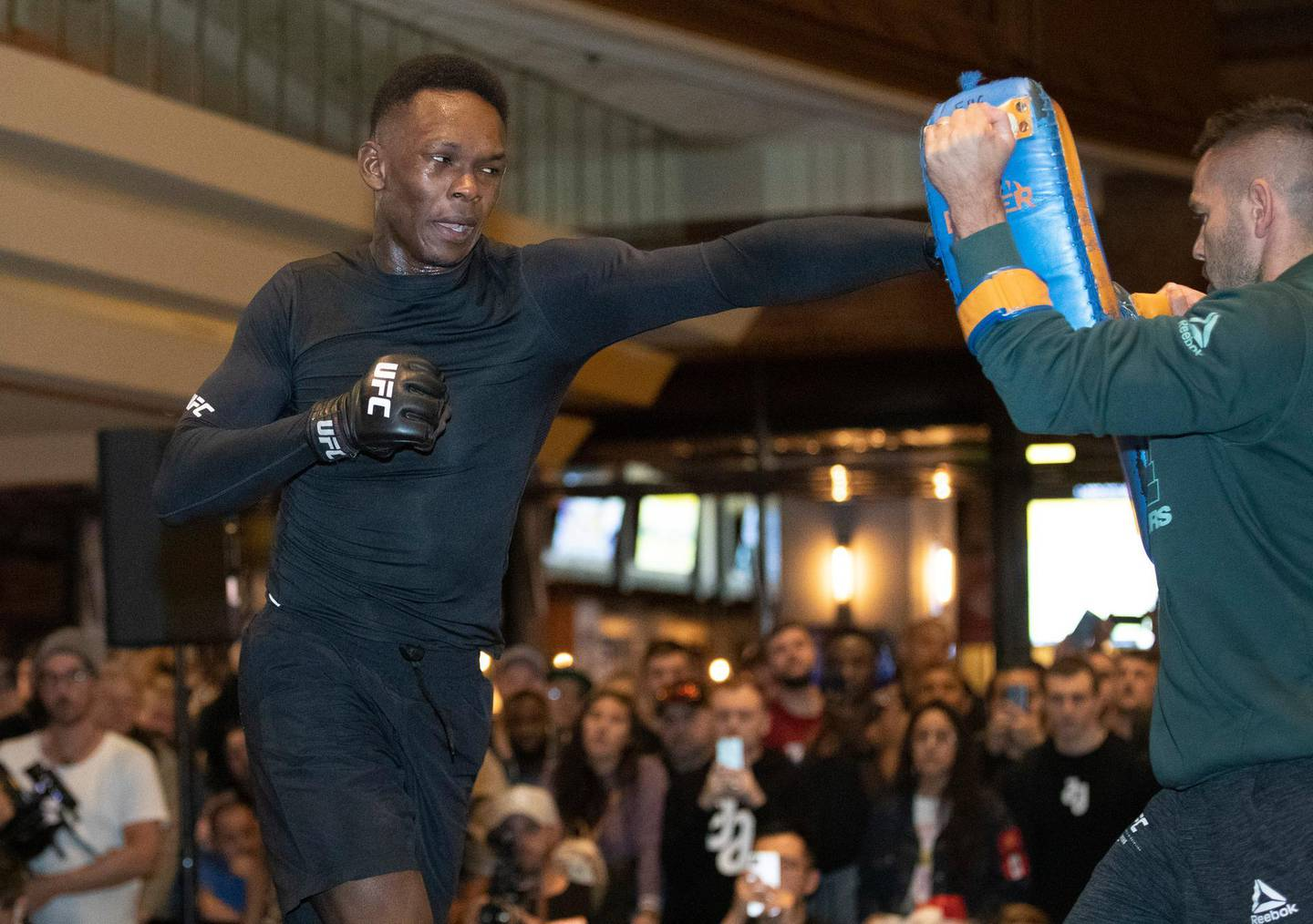 UFC middleweight champion Israel Adesanya, left, of Nigeria, works on his timing with coach Andrei Paulet during UFC 248 open workouts, in Las Vegas on Wednesday, March 4, 2020. (Steve Marcus/Las Vegas Sun via AP)