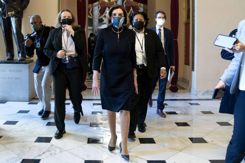 WASHINGTON, DC - JANUARY 13: Speaker of the House Nancy Pelosi (D-CA) (C) wears a protective mask while walking to the House Floor at the U.S. Capitol on January 13, 2021 in Washington, DC. The House of Representatives is expected to vote to impeach President Donald Trump later today, after Vice President Mike Pence declined to use the 25th amendment to remove him from office after protestors breached the U.S. Capitol last week.   Stefani Reynolds/Getty Images/AFP == FOR NEWSPAPERS, INTERNET, TELCOS & TELEVISION USE ONLY ==