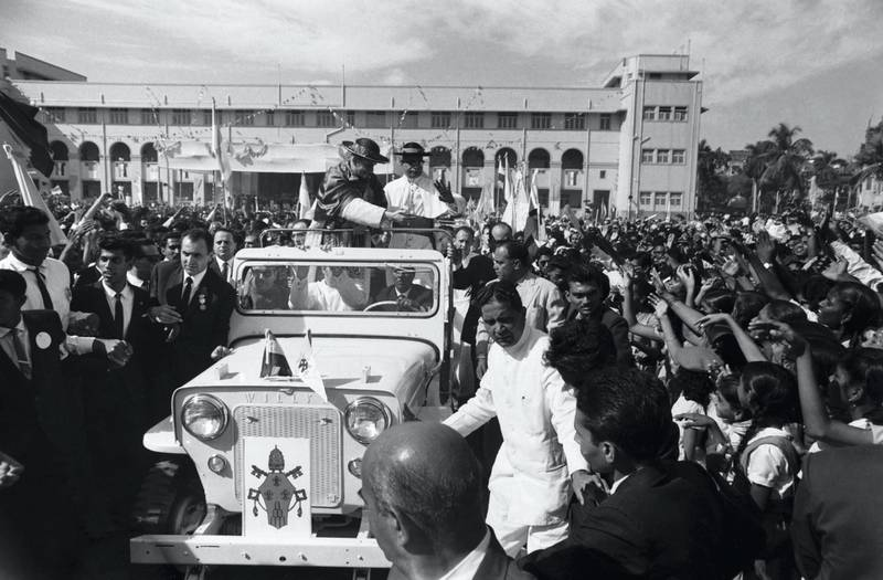A crowd of people gather round the vehicle carrying Pope Paul VI who is visiting the John Bosco School. (Photo by Hulton-Deutsch/Hulton-Deutsch Collection/Corbis via Getty Images)