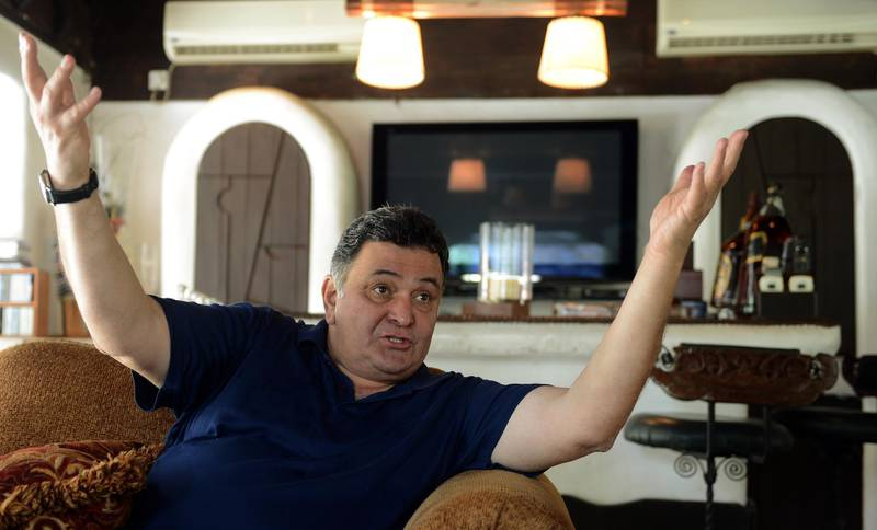 """TO GO WITH India-entertainment-Bollywood-dynasties-100years,FOCUS by Rachel O'Brien In this picture taken on April 29, 2013, India's Bollywood actor Rishi Kapoor gestures as he speaks during an interview with AFP at his house in Mumbai. From a cinema pioneer and India's Charlie Chaplin, one powerful Bollywood family can trace the roots of their stardom almost right back to the birth of the film industry 100 years ago. """"We have been there throughout. All the milestones of cinema, there has been some Kapoor or the other,"""" says 60-year-old Rishi Kapoor, who has notched up nearly 150 Hindi film credits over a four-decade acting career.   AFP PHOTO/PUNIT PARANJPE (Photo by PUNIT PARANJPE / AFP)"""