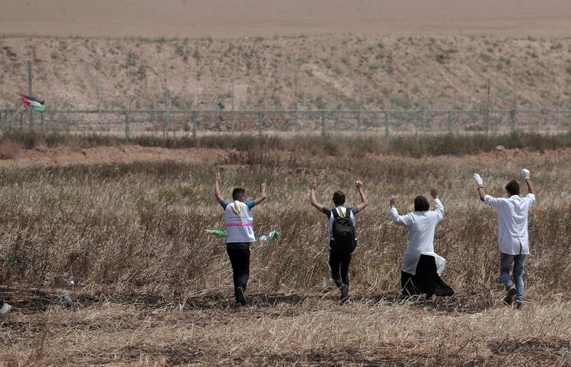 Palestinian medics raise their hands toward the fence to evacuate a wounded youth during clashes with Israeli troops along Gaza's border with Israel, Friday, April 13, 2018. Thousands of Palestinians staged a mass protest along Gaza's sealed border with Israel on Friday, some burning Israeli flags, and Israeli soldiers fired tear gas and live bullets from across the border fence. (AP Photo/Adel Hana)