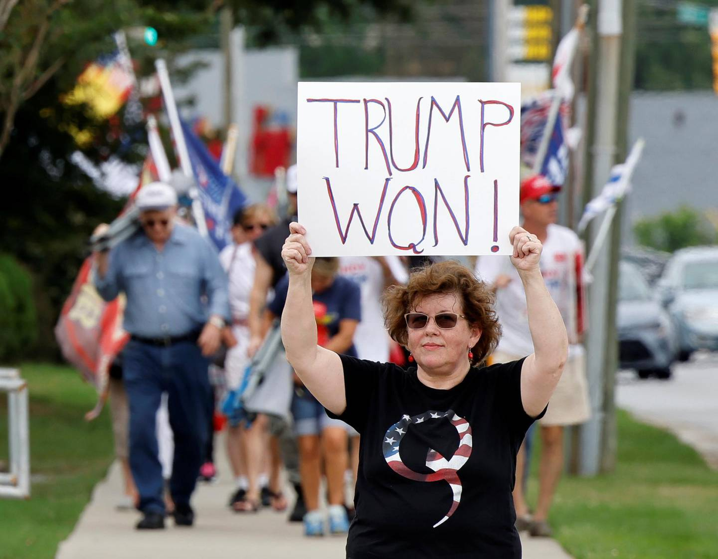 A supporter of former U.S. President Donald Trump wears a QAnon shirt while holding a sign stating he won the 2020 election, outside the North Carolina GOP convention in Greenville, North Carolina, U.S. June 5, 2021.  REUTERS/Jonathan Drake