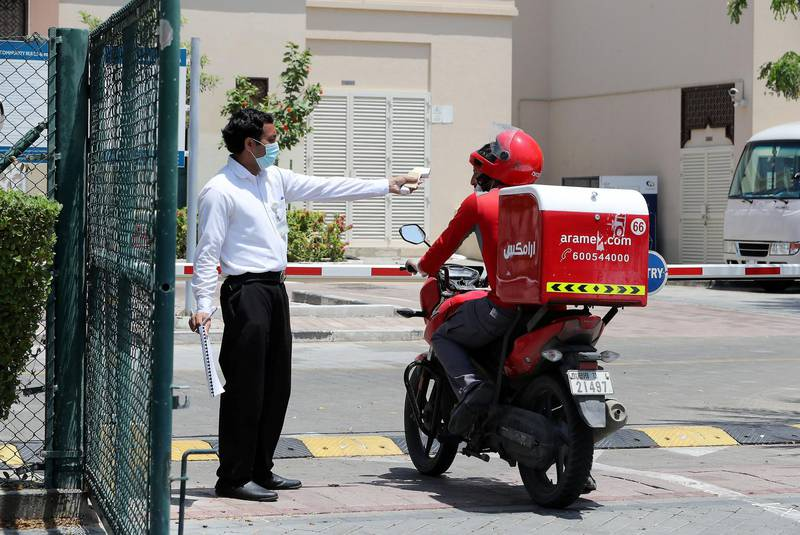 DUBAI, UNITED ARAB EMIRATES , April 17– 2020 :- One of the security guard taking  body temperature of the delivery driver in Al Furjan area in Dubai. Dubai is conducting 24 hours sterilisation programme across all areas and communities in the Emirate and told residents to stay at home. UAE government told residents to wear face mask and gloves all the times outside the home whether they are showing symptoms of Covid-19 or not.  (Pawan Singh / The National) For News/Online/Instagram