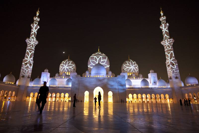 People enjoy a light show projected on the walls of the Sheikh Zayed Mosque on Tuesday evening, Nov. 29, 2011, in celebration of the upcoming 40th anniversary of the UAE creation at the mosque in Abu Dhabi. (Silvia Razgova/The National)