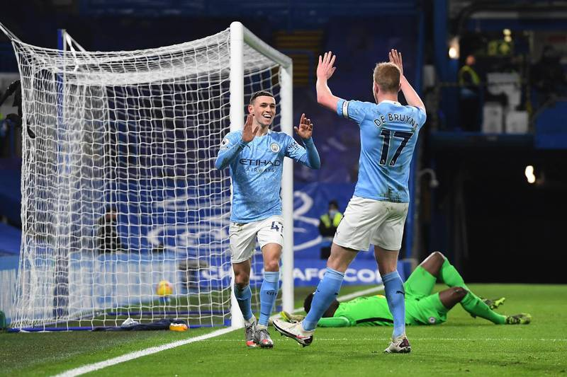 LONDON, ENGLAND - JANUARY 03: Phil Foden (l) of Manchester City celebrates with team mate Kevin De Bruyne (r) after scoring their sides second goal during the Premier League match between Chelsea and Manchester City at Stamford Bridge on January 03, 2021 in London, England. The match will be played without fans, behind closed doors as a Covid-19 precaution. (Photo by Andy Rain - Pool/Getty Images)