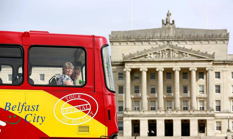 A tour bus makes its way past Parliament Buildings on the Stormont Estate in Belfast, Northern Ireland, September 14, 2015. REUTERS/Cathal McNaughton - LR2EB9E0ZTXR4