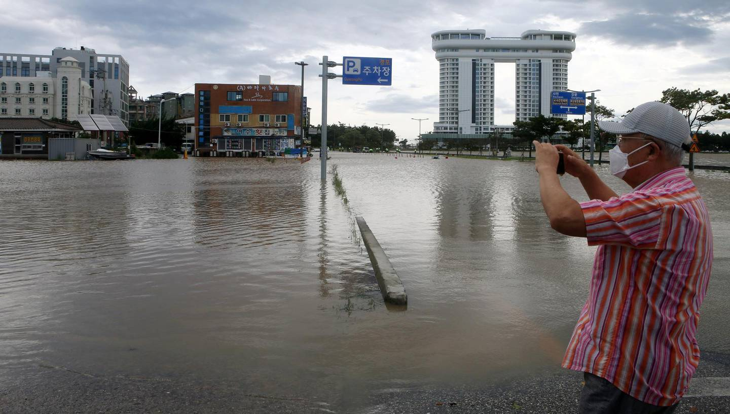 A man takes a photo of a submerged parking lot by Typhoon Maysak in Gangneung, South Korea, September 3, 2020.    Yonhap via REUTERS   ATTENTION EDITORS - THIS IMAGE HAS BEEN SUPPLIED BY A THIRD PARTY. SOUTH KOREA OUT. NO RESALES. NO ARCHIVE.
