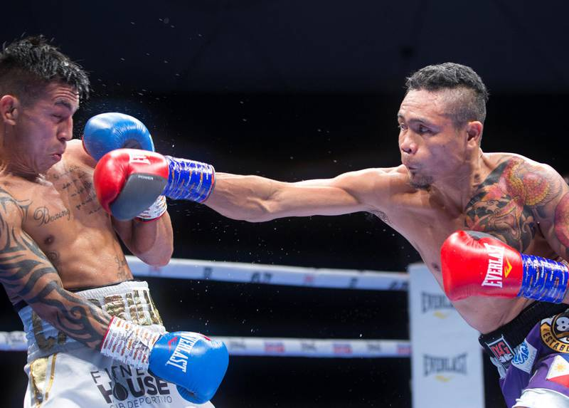 Dubai, United Arab Emirates - Donnie Nietes of the Philippines (right) hitting Pablo Carillo of Colombia at the Rotunda, Ceasar's Palace, Bluewaters Island, Dubai.  Leslie Pable for The National