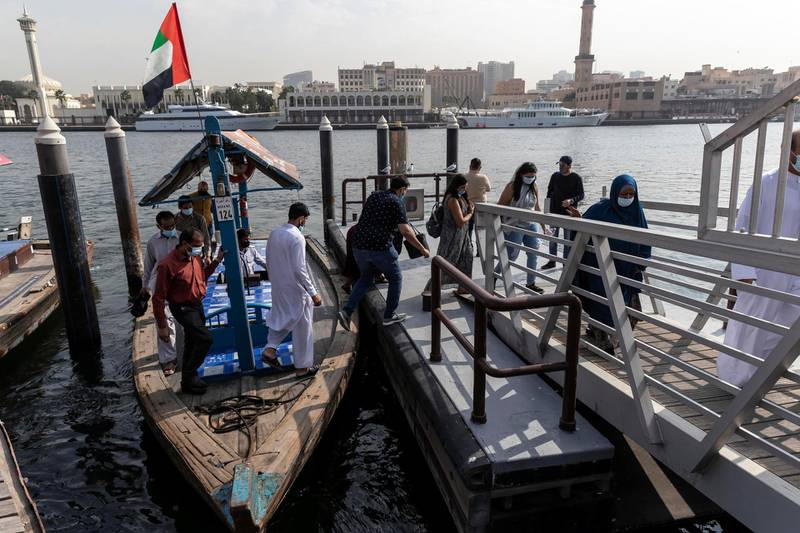 DUBAI, UNITED ARAB EMIRATES. 25 FEBRUARY 2021. COVID - 19 Standalone. Deira souk during the time of Covid. Commuters wearing face mask disembark an abra. (Photo: Antonie Robertson/The National) Journalist: Nick Webster. Section: National.