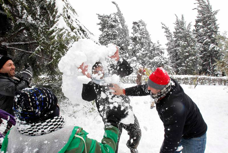 Men play with snow after a heavy snowstorm in Amman January 10, 2013. Snowstorms and heavy rain have caused the closure of main streets in the capital Amman and other cities over the past two days. REUTERS/Ali Jarekji  (JORDAN - Tags: ENVIRONMENT) *** Local Caption ***  AMM30_JORDAN-_0110_11.JPG