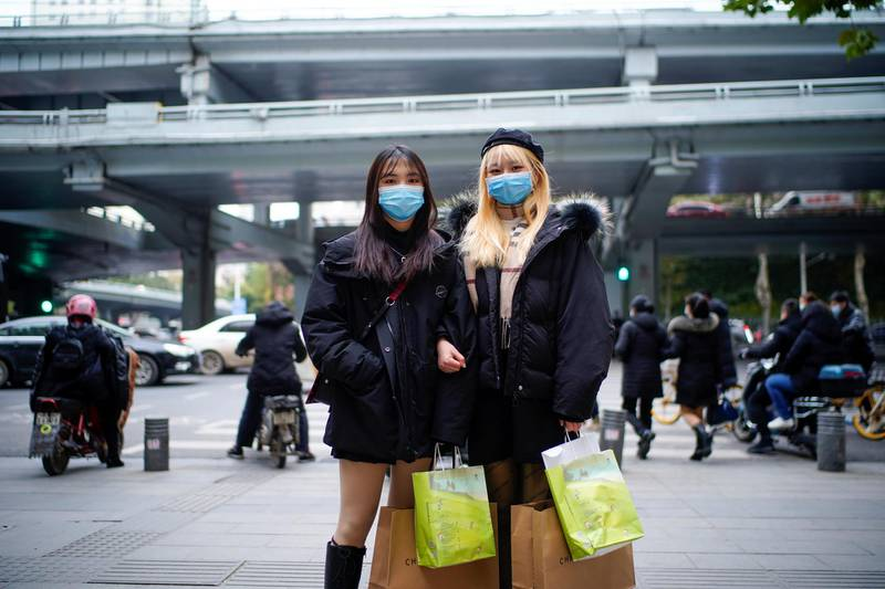 """Wu Mengjing, 22, (R) a student poses with her friend on a street, almost a year after the global outbreak of the coronavirus disease (COVID-19) in Wuhan, Hubei province, China December 16, 2020. """"I was shocked when the epidemic broke out in January. As a student in Wuhan, I was also very sad and hoped to make some contributions to the epidemic in Wuhan and the whole country,"""" Mengjing said. Picture taken December 16, 2020. REUTERS/Aly Song"""