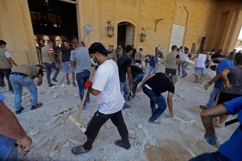People clean debris at Mohammed al-Amin mosque in the centre of Beirut on August 5, 2020 in the aftermath of a massive explosion in the Lebanese capital. Rescuers searched for survivors in Beirut after a cataclysmic explosion at the port sowed devastation across entire neighbourhoods, killing more than 100 people, wounding thousands and plunging Lebanon deeper into crisis. The blast, which appeared to have been caused by a fire igniting 2,750 tonnes of ammonium nitrate left unsecured in a warehouse, was felt as far away as Cyprus, some 150 miles (240 kilometres) to the northwest.  / AFP / JOSEPH EID