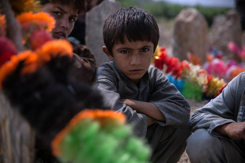 Lal Agha, 8, sits by the grave of his father Khyber, 25, who was killed in a US drone strke last week.