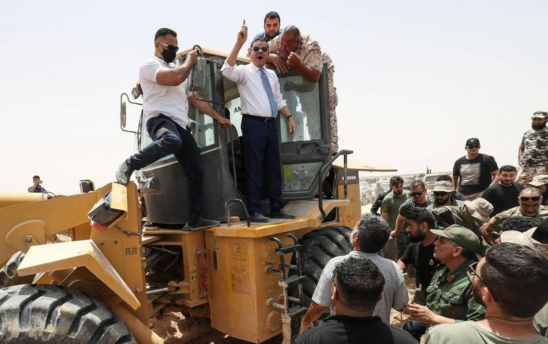 Libyan Interim Prime Minister Abdulhamid Dbeibah, waves as he stands atop an excavator on June 20, 2021, in the town of Buwairat al-Hassoun, during a ceremony to mark the reopening of 300-kilometre road between the cities of Misrata and Sirte,  Libya's unity government today reopened the coastal highway linking the country's east and west, that was cut off in 2019 as eastern-based military strongman Khalifa Haftar launched an offensive to seize the capital Tripoli.  It connects the war-torn North African country's border with Tunisia to its frontier with Egypt. / AFP / Mahmud TURKIA