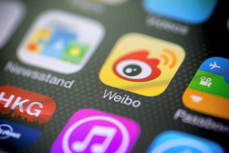 Sina Corp.'s Sina Weibo microblogging service app icon is displayed on an Apple Inc. iPhone 5s in an arranged photograph in Hong Kong, China, on Tuesday, April 22, 2014. Weibo Corp., the Chinese microblogging service owned by Sina Corp. and Alibaba Group Holdings Ltd., raised $285.6 million its U.S. initial public offering after pricing the shares at the low end of a marketed range, people with knowledge of the matter said. Photographer: Brent Lewin/Bloomberg