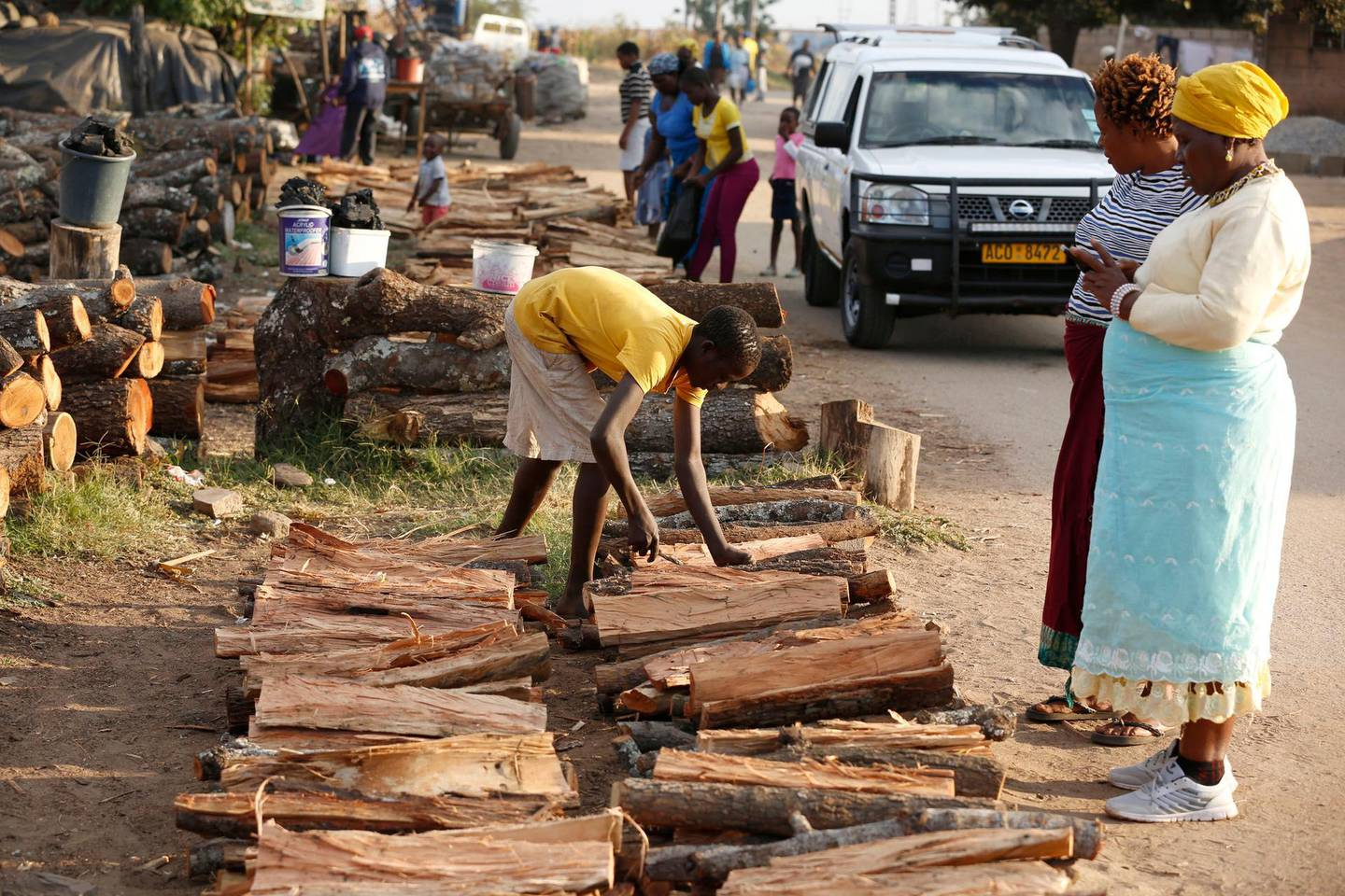 epa07586967 Women buy firewood in Tafara, Zimbabwe, 18 May 2019 (issued 20 May 2019) as power cuts continue. The Zimbabwe Electricity Transmission and Distribution Company (ZETDC), citing reduced output at its largest hydro plant and ageing coal-fired generators, said power cuts which started a week now would last up to eight hours during morning and evening peak periods. This has led to massive disruption of production and has also led to a huge demand of firewood and liquid petroleum gas.  EPA/AARON UFUMELI