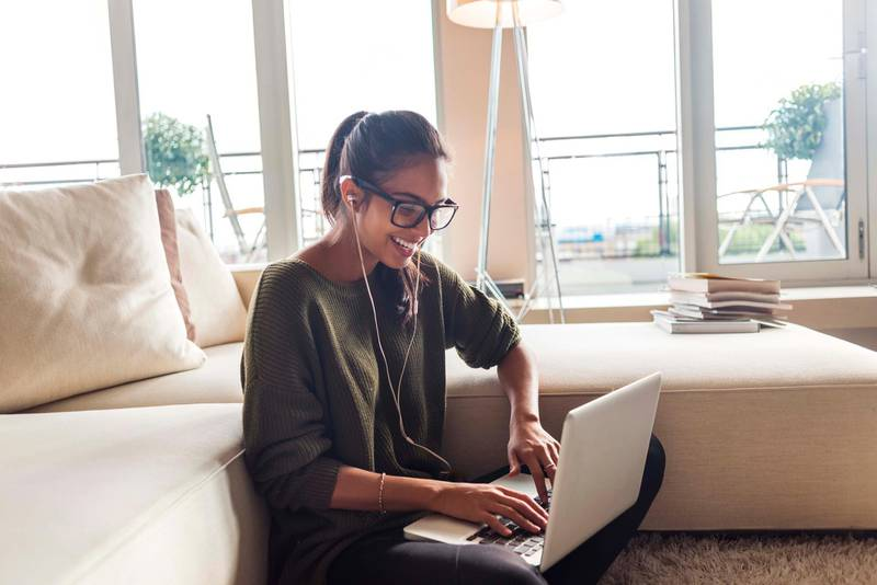 happy young woman using her laptop at home,sitting on the carpet in her living room. Getty Images
