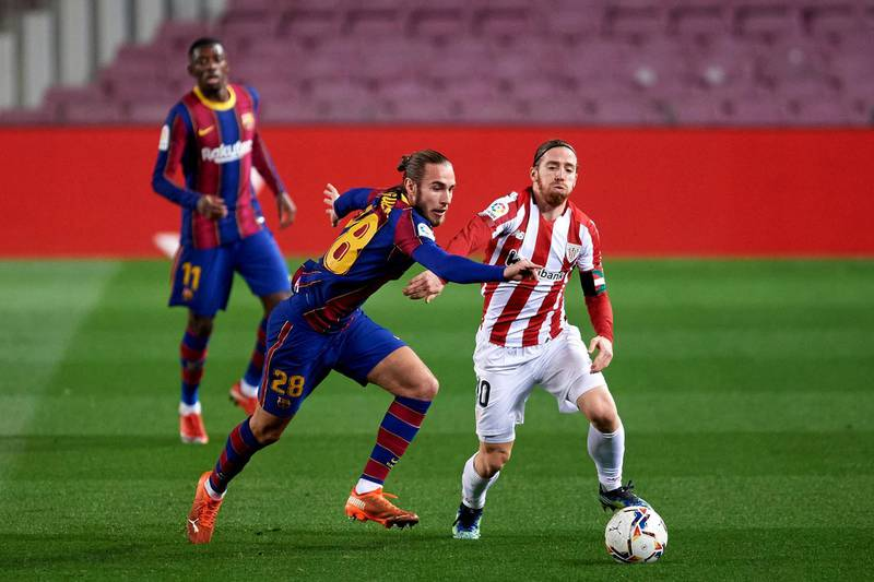 BARCELONA, SPAIN - JANUARY 31: Oscar Mingueza of FC Barcelona battles for the ball with Iker Muniain of Athletic Club during the La Liga Santander match between FC Barcelona and Athletic Club at Camp Nou on January 31, 2021 in Barcelona, Spain. Sporting stadiums around Spain remain under strict restrictions due to the Coronavirus Pandemic as Government social distancing laws prohibit fans inside venues resulting in games being played behind closed doors. (Photo by Alex Caparros/Getty Images)