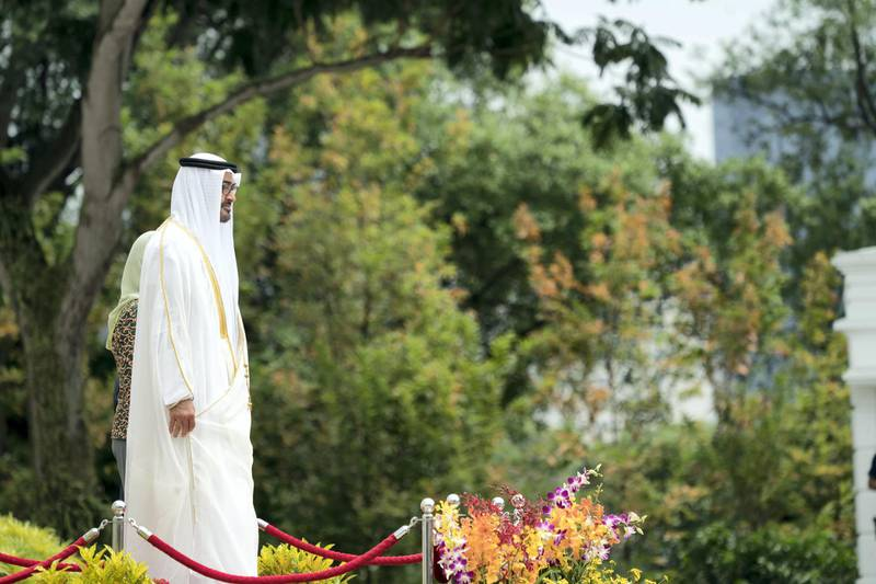 SINGAPORE, SINGAPORE - February 28, 2019: HH Sheikh Mohamed bin Zayed Al Nahyan, Crown Prince of Abu Dhabi and Deputy Supreme Commander of the UAE Armed Forces (L) and HE Halimah Yacob, President of Singapore (back L - partially hidden), stand for the national anthem, during a reception at the Istana presidential palace.  ( Eissa Al Hammadi for the Ministry of Presidential Affairs ) ---