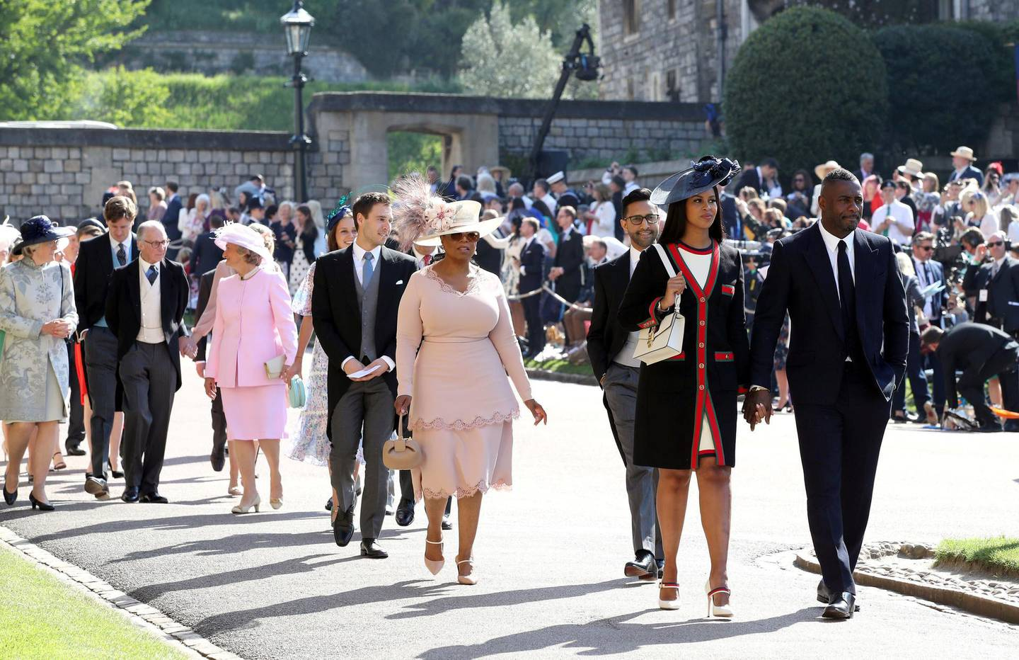 WINDSOR, UNITED KINGDOM - MAY 19: Idris Elba and Sabrina Dhowre followed by Oprah Winfrey (fourth right) arrive at St George's Chapel at Windsor Castle for the wedding of Meghan Markle  and Prince Harry on May 19, 2018 in Windsor, England. (Photo by Chris Radburn - WPA Pool/Getty Images)