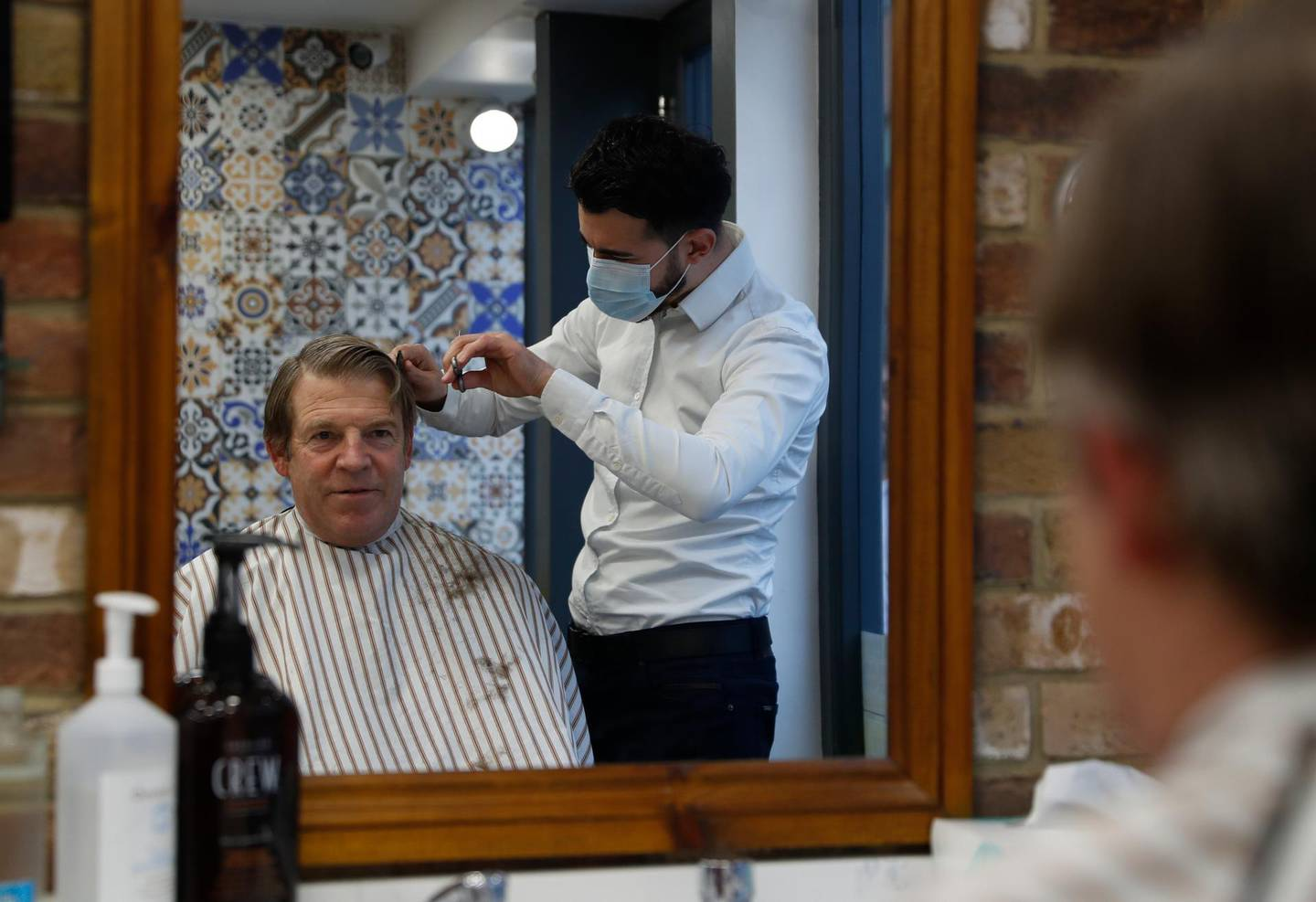 The Lord Mayor of London William Russell gets his hair cut by Ali Baltar, owner of the Grooming Lounge in the City of London, Monday, April 12, 2021. Millions of people in England will get their first chance in months for haircuts, casual shopping and restaurant meals on Monday, as the government takes the next step on its lockdown-lifting road map. (AP Photo/Alastair Grant)