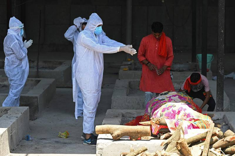 A family member wearing protective gear performs final rites on the funeral pyre of a Covid-19 coronavirus victim at a crematorium in New Delhi on May 24, 2021, as India passed more than 300,000 deaths from coronavirus pandemic. / AFP / Sajjad HUSSAIN