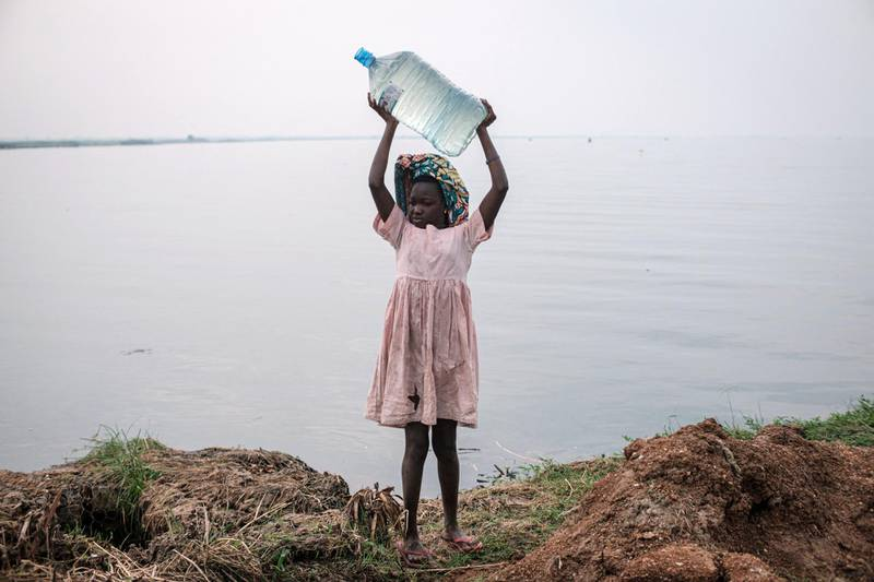 A girl holds a bottle of water above her head after fetching water from the Nile river near the Kisomere village in western Uganda, on January 28, 2020. - When exploitable crude oil deposits were discovered in 2006 in the Lake Albert region, Uganda began to imagine itself as a new oil Eldorado. But 14 years later, the mirage has faded, and it is still waiting to extract its first drops of black gold. This discovery had raised wild hopes in a country where 21% of the population lives in extreme poverty. The Ugandan government saw the prospect of earning at least $1.5 billion a year and increasing its GDP per capita from $630 to over $1,000. (Photo by Yasuyoshi CHIBA / AFP)