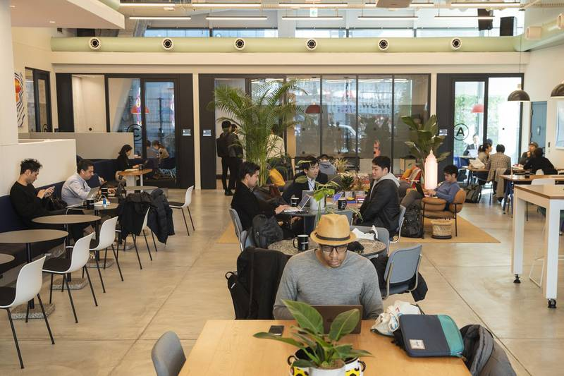 Members sit and use laptop computers at the WeWork Cos. Iceberg co-working space in Tokyo, Japan, on Thursday, Dec. 20, 2018. The office-sharing giant, valued at as much as $42 billion, is getting a greater portion of its business from the large companies that property owners usually court. It's also building an investment division to buy its own sites, according to people with knowledge of the matter. Photographer: Keith Bedford/Bloomberg