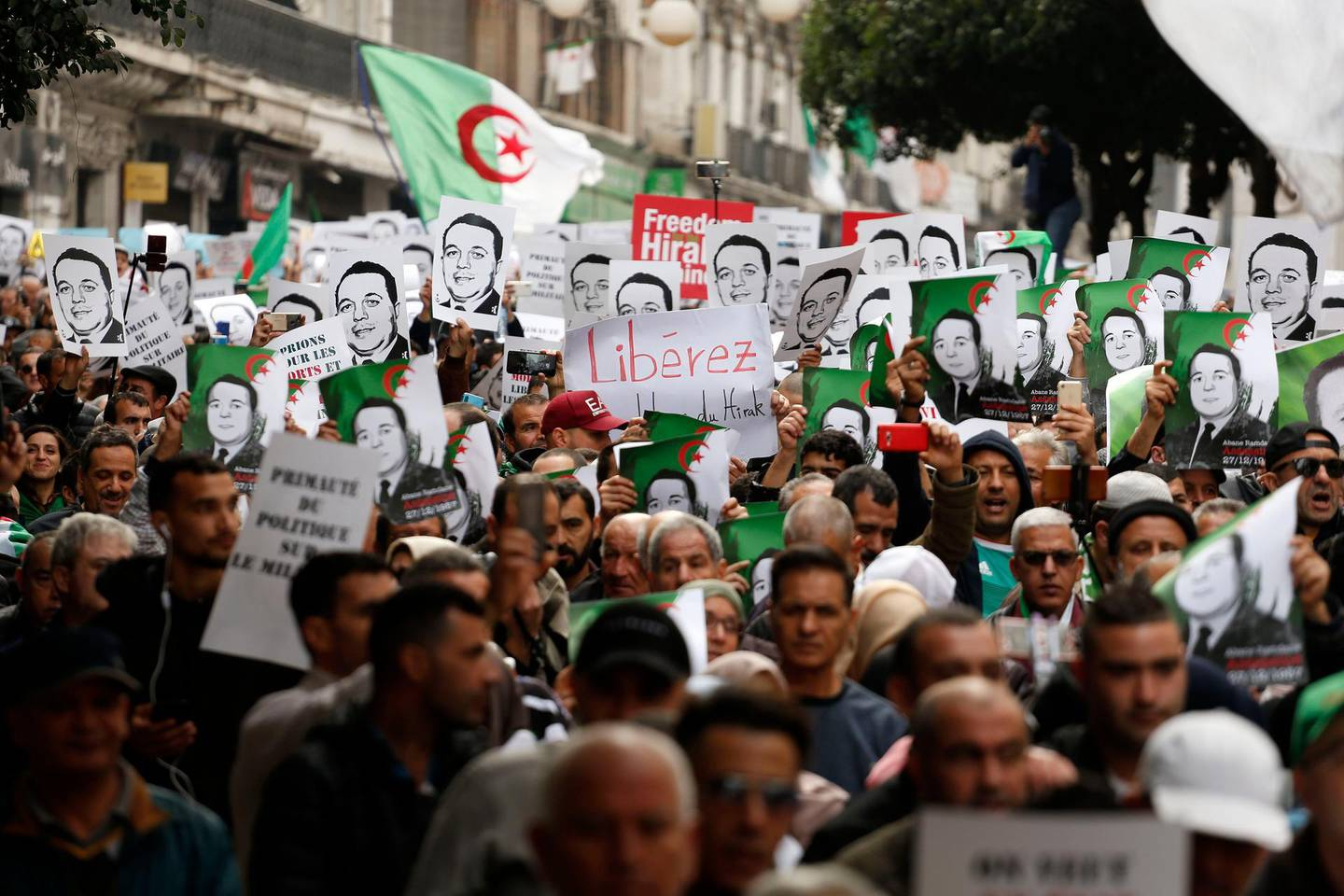 Protesters carry photos of political detainees as they take to the streets in the capital Algiers to reject the presidential elections and protest against the government, in Algeria, Friday, Dec. 27, 2019. (AP Photo/Toufik Doudou)