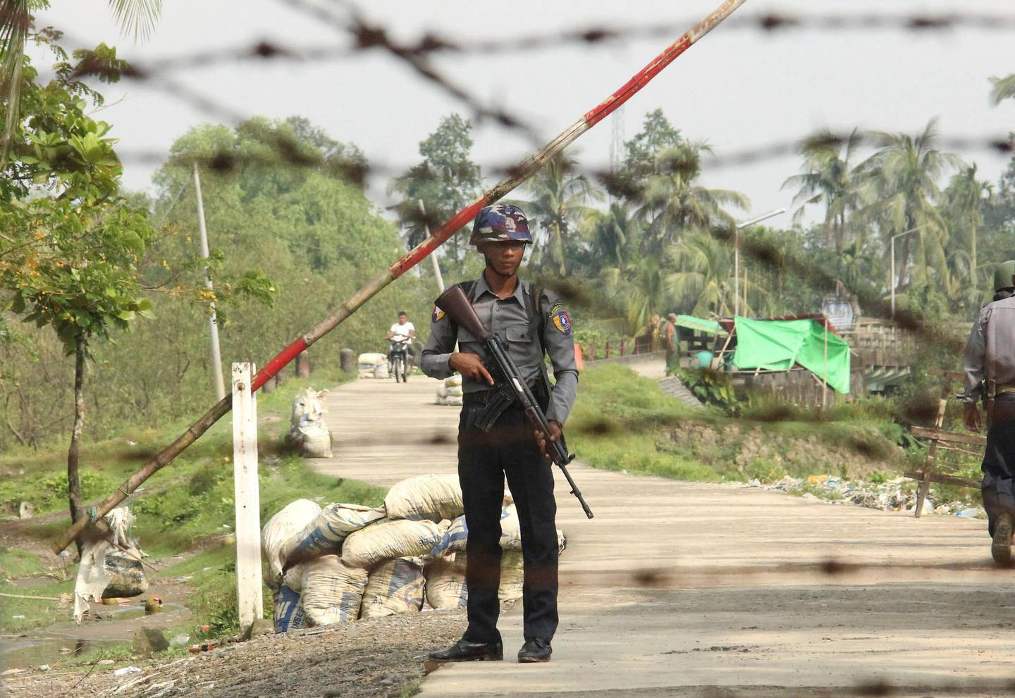 FILE - In this Sept. 6, 2017, file photo, a Myanmar police officer stands guard at a checkpoint in Shwe Zar village in the northern Rakhine state of Myanmar. Amnesty International, in a report issued Wednesday, May 29, 2019, says it has found new evidence of war crimes and human rights violations in Rakhine State, where the armed forces two years ago carried out a brutal counterinsurgency campaign that drove more than 700,000 members of the Muslim Rohingya minority to flee across the border to Bangladesh. (AP Photo/File)