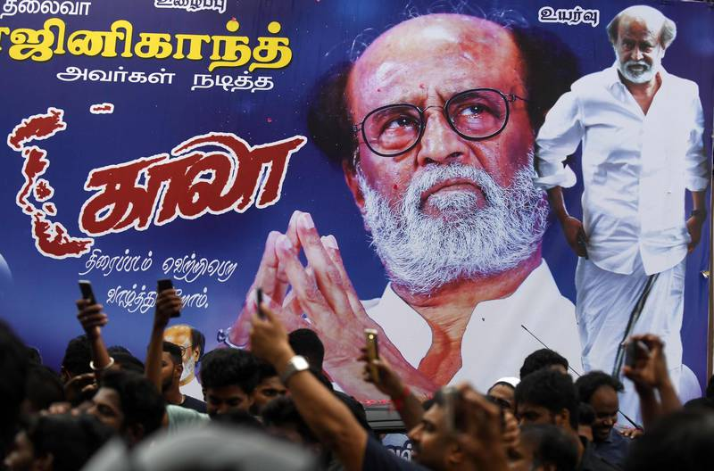"""Indian fans of Bollywood star Rajinikanth gather outside a cinema on the first day of release of his new Tamil-language film """"Kaala"""", in Chennai on June 7, 2018. Rajinikanth's film """"Kaala"""" is released on June 7 across the country except in Karnataka as Pro-Kannada groups have been upset with Rajinikanth's remarks on the Cauvery water dispute between Karnataka and Tamil Nadu. / AFP / Arun SANKAR"""
