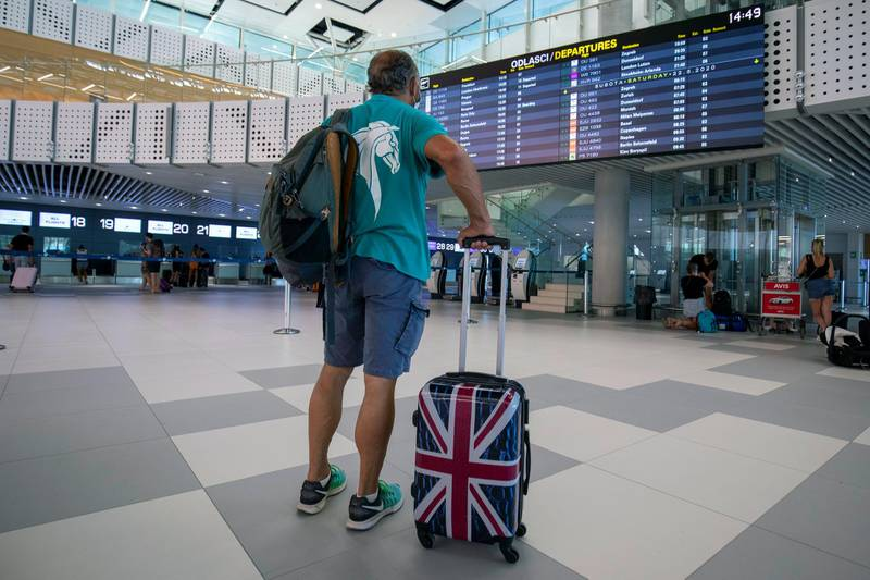 FILE - In this Friday, Aug. 21, 2021 file photo, a passenger inspects the departures timetable at the international airport in Split, Croatia. Airlines and holiday providers on Friday, June 25, 2021 expressed frustration with the U.K.'s plans to ease travel restrictions, saying uncertainty about how and when the new rules will be implemented make it difficult for people to book summer vacations. (AP Photo/Miroslav Lelas, File)