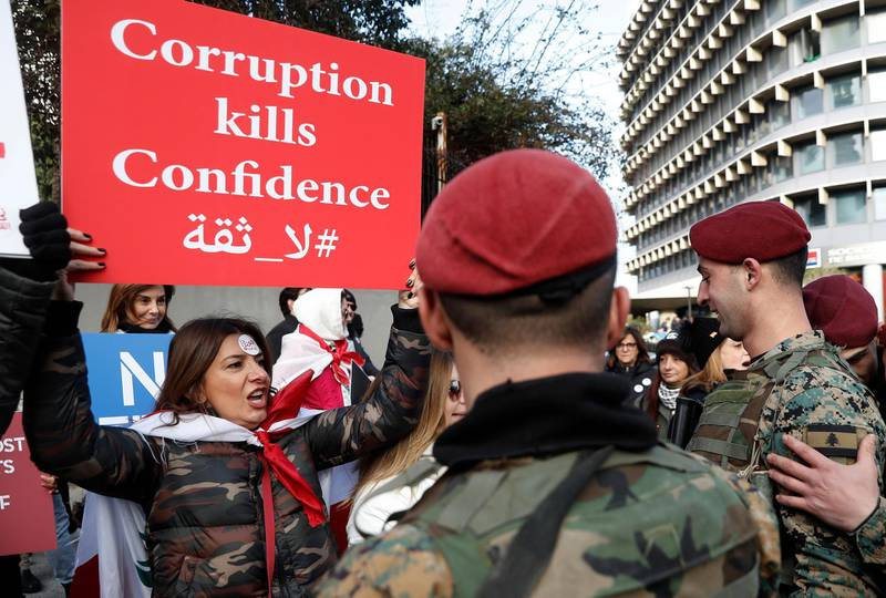 FILE - In this February 11, 2020 file photo, an anti-government protester shouts slogans as she holds a placard in front of Lebanese army soldiers, in downtown Beirut, Lebanon, Lebanon's government agreed Tuesday to hire a New York-based company to conduct a forensic audit of the country's central bank accounts to determine how massive amounts of money were spent in the nation plagued by corruption. (AP Photo/Hussein Malla, File)