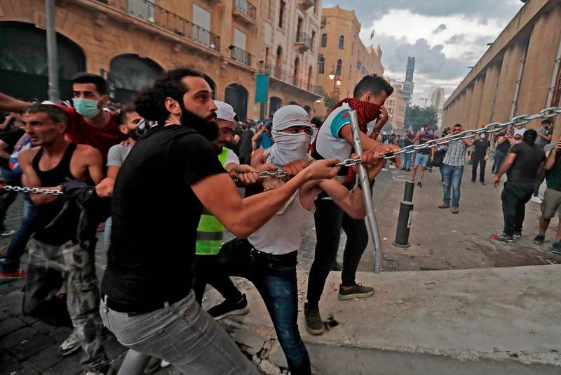 Lebanese protesters try to storm the vicinity of the parliament in central Beirut on August 10, 2020 following a huge chemical explosion that devastated large parts of the Lebanese capital.  / AFP / JOSEPH EID