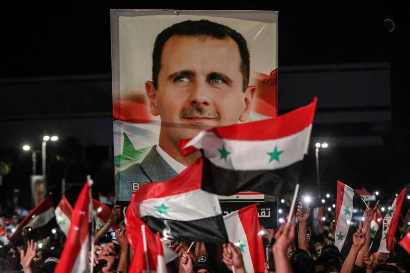 TOPSHOT - Syrians wave national flags and carry a large portrait of their president as they celebrate in the streets of the capital Damascus, a day after an election set to give the current President Bashar al-Assad a fourth term, on May 27, 2021. The election held yesterday in government-held areas was the second presidential vote in Syria since the start in 2011 of a war that has left over 388,000 dead.  / AFP / LOUAI BESHARA