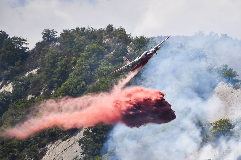 A firefighting aircraft drops flame retardant to put out a fire in Rigaud, north of Nice, southeastern France, on August 3, 2017. France has been battling for several weeks huge fires near beaches popular with tourists on the Cote d'Azur, forcing the evacuation of people. / AFP PHOTO / Yann COATSALIOU