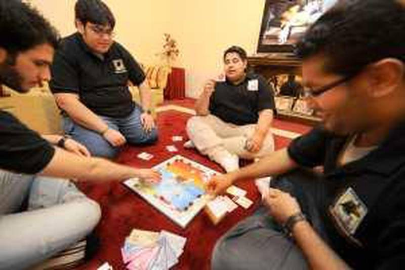 SEPTEMBER 12, 2009, KUWAIT: Young Kuwaiti guys (check with James Calderwood for names) play with there new monopoly  who started selling a local version of it in Kuwait. Raed Qutena for The National *** Local Caption ***  RQC_8717.JPG