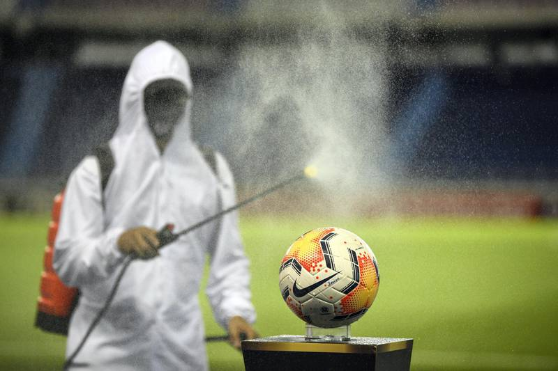 A worker disinfects the balls before the closed-door Copa Libertadores group phase football match between Colombia's Junior and Ecuador's Barcelona at the Roberto Melendez Stadium in Barranquilla, Colombia, on September 30, 2020, amid the COVID-19 novel coronavirus pandemic. (Photo by Raul ARBOLEDA / AFP)
