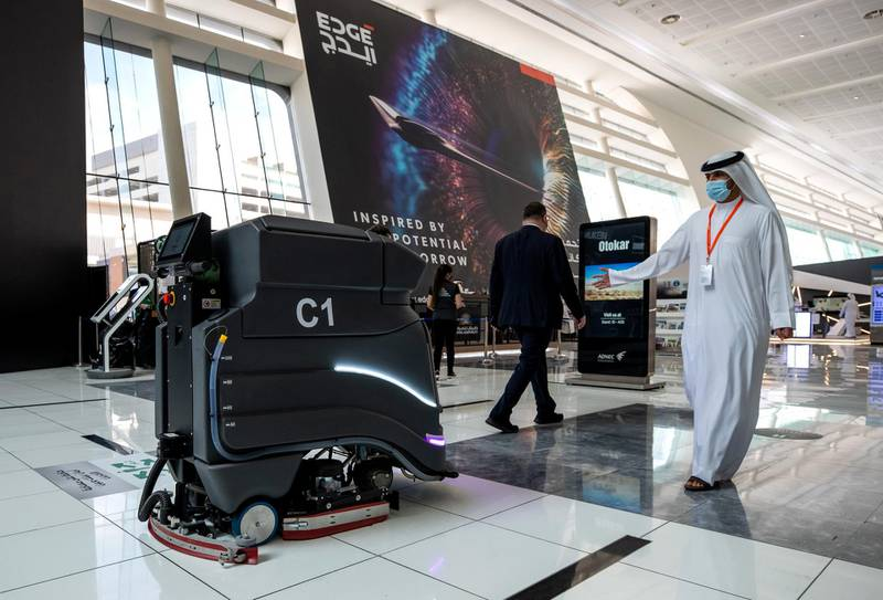 Abu Dhabi, United Arab Emirates, February 21, 2021.  Idex 2021, the first major in-person exhibition held in Abu Dhabi since the start of the Covid-19 pandemic, opened its doors to delegates on Sunday morning.  A visitor checks out a robot mopping the floor.Victor Besa / The NationalSection:  NAReporter:  John Dennehy