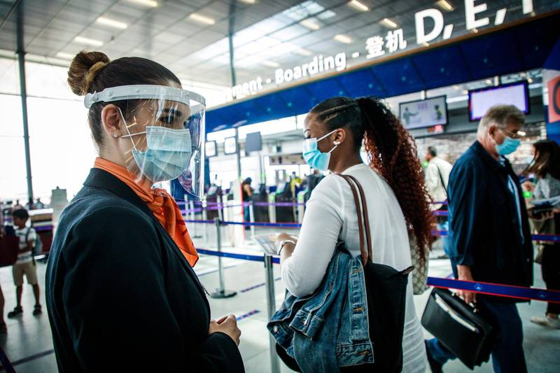 epa08510602 A hostess wearing a face mask guides passengers at Orly airport, near Paris, France, 26 June 2020. The Paris airport resumes its activity after more than three months of closure since the outbreak of the COVID-19 pandemic in France.  EPA/CHRISTOPHE PETIT TESSON