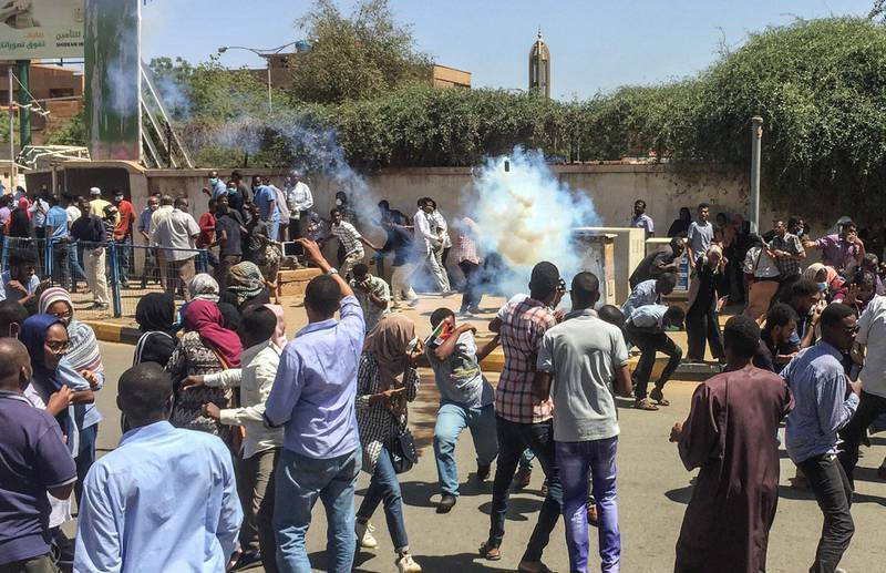 Sudanese protesters run for cover from tear gas canisters fired by police outside the military headquarters in the capital Khartoum on April 6, 2019. - Protests have rocked the east African country since December, with angry crowds accusing Bashir's government of mismanaging the economy that has led to soaring food prices and regular shortages of fuel and foreign currency. (Photo by - / AFP)