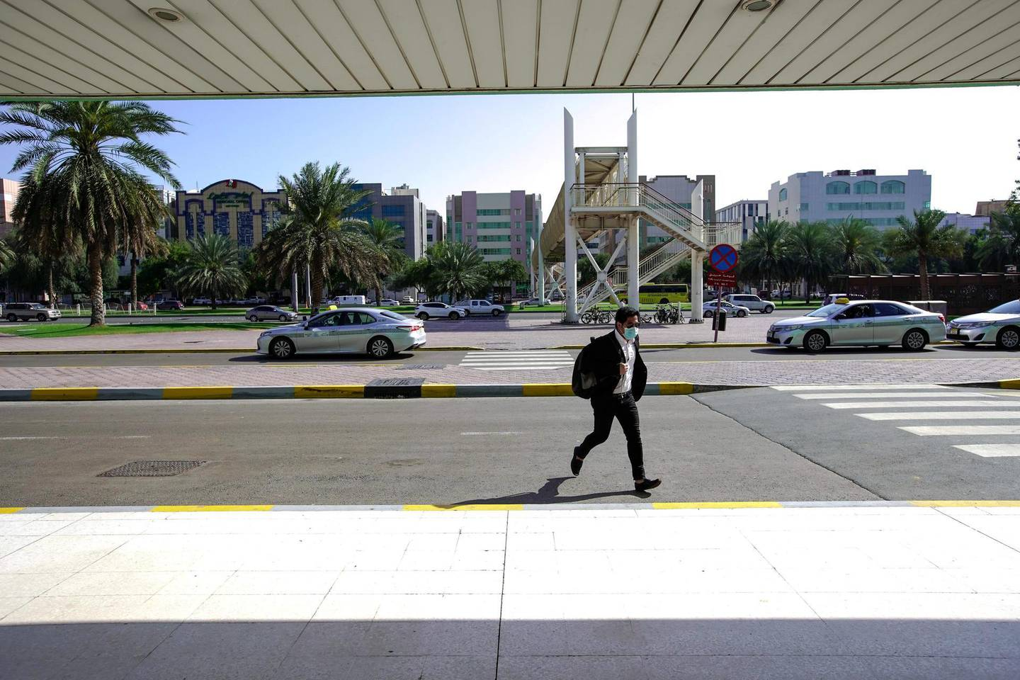 """Abu Dhabi, United Arab Emirates, March 24, 2020. Standalone: Coronavirus   A commuter crosses the street at the AUH Central Bus Terminal.  Both automobile and pedestrian traffic has noticeably decreased at downtown Abu Dhabi due to the strict """"stay at home"""" orders the UAE government has implemented to combat the spread of coronavirus.Victor Besa / The NationalSection:  NA"""