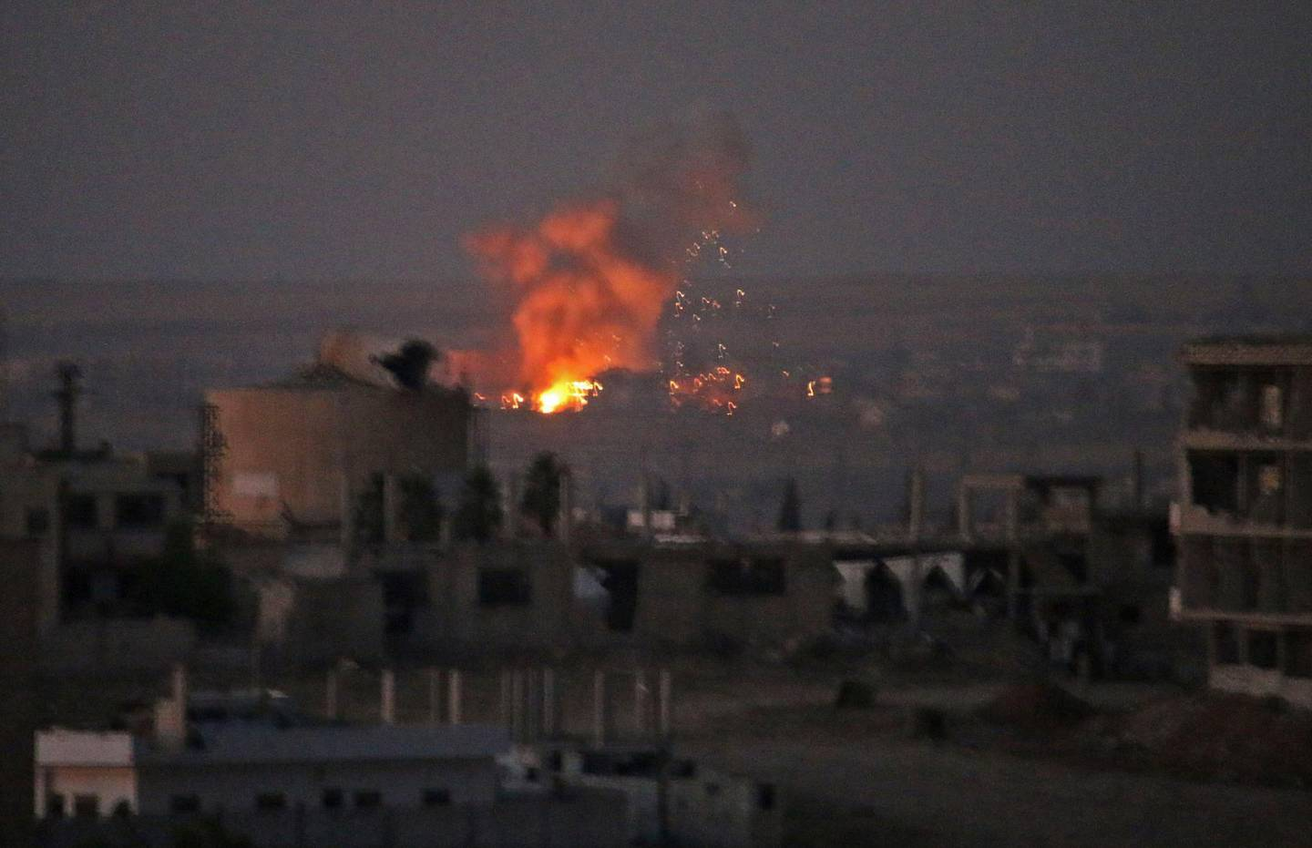 TOPSHOT - This picture shows an explosion in rebel-held areas of the city of Daraa during reported airstrikes by Syrian regime forces on July 5, 2018. Waves of air strikes pounded rebel-held areas of southern Syria after the failure a day earlier of Russian-brokered talks to end the offensive in Daraa province, which has killed dozens and forced tens of thousands from their homes. / AFP / MOHAMAD ABAZEED