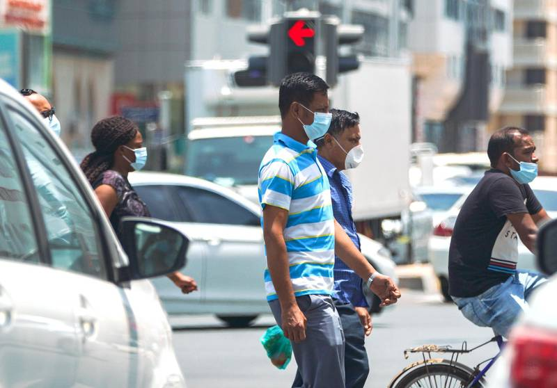 Abu Dhabi, United Arab Emirates, June 3, 2020.   Pedestrians protect themselves with face masks during the Covid-19 pandemic while crossing the street at downtown Abu Dhabi.Victor Besa  / The NationalSection:  Standalone / Stock