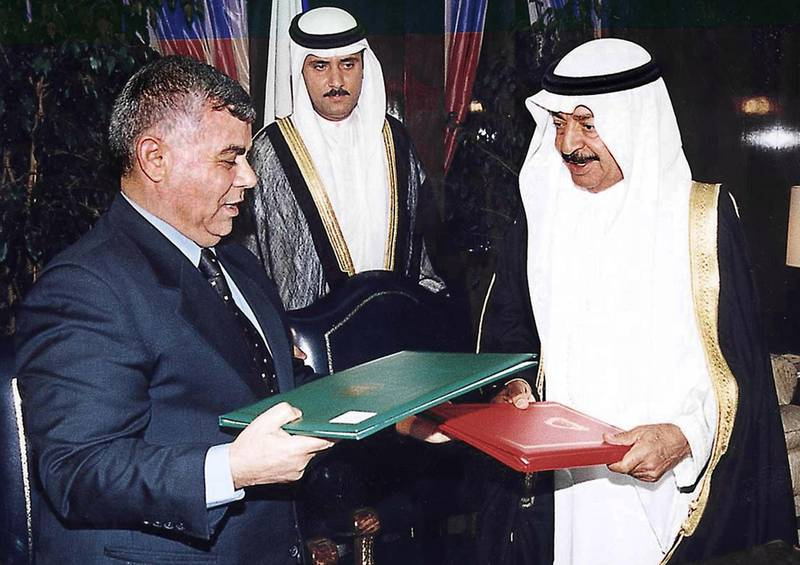Syrian Prime Minister Mohammed Mustafa Miro (L) and his Bahraini counterpart Khalifa bin Salman al-Khalifa (R) exchange a cooperation agreement they signed in Manama 21 September 2000. The two countries are set to increase cooperation in all fields with the establishment of a joint commission, according to a statement issued by the two sides before Miro left Bahrain, at the end of a 24-hour visit to the Gulf emirate. (Photo by GNA / AFP)