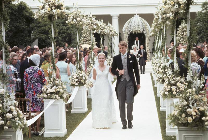 (Original Caption) Washington, DC.: After taking their vows, Edward Finch Cox and Tricia Nixon Cox walk through rows of flowers past their guests en route to the White House for the reception, following their wedding in the White House rose garden. The bride is the daughter of president Richard Nixon.