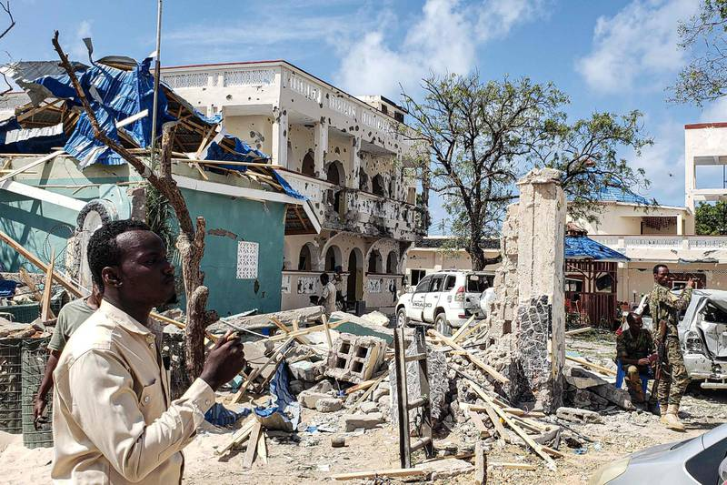 A man passes in front of the rubbles of the popular Medina hotel of Kismayo after on July 13, 2019, a day after at least 26 people, including several foreigners, were killed and 56 injured in a suicide bomb and gun attack claimed by Al-Shabaab militants. A suicide bomber rammed a vehicle loaded with explosives into the Medina hotel in the port town of Kismayo before several heavily armed gunmen forced their way inside, shooting as they went, authorities said. / AFP / -