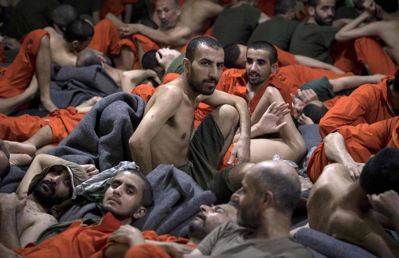 Men, allegedly affiliated with the Islamic State (IS) group, sit on the floor in a prison in the northeastern Syrian city of Hasakeh on October 26, 2019. Kurdish sources say around 12,000 IS fighters including Syrians, Iraqis as well as foreigners from 54 countries are being held in Kurdish-run prisons in northern Syria.  / AFP / FADEL SENNA